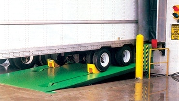 A truck at a loading dock with vehicle restraints